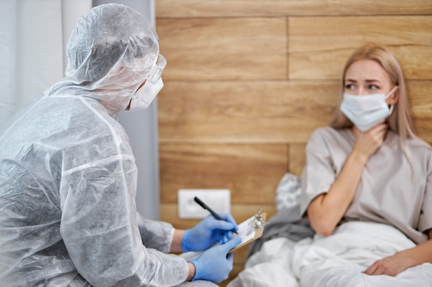 Doctor in protective suit asks patient about state of health, professional doctor taking notes, coronavirus covid-19. stay at home concept during pandemic and self isolation. focus on doctor