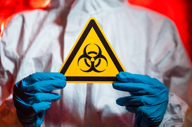 A doctor in a protective suit holds a biohazard sign. coronavirus pandemic concept, quarantine