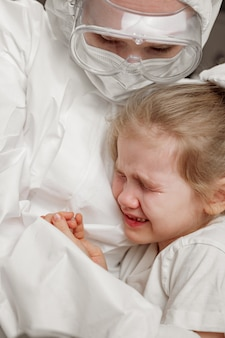 The doctor in a protective suit, mask, gloves and glasses calms down, hugs a little sick girl.