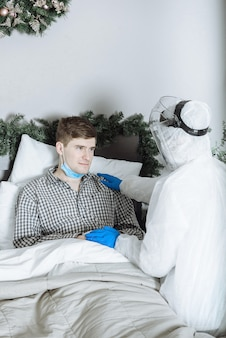 A doctor in a protective suit ppe hazmat examines a sick patient with coronavirus covid-19