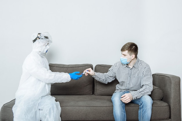 A doctor in a protective suit ppe hazmat wearing a mask and glasses gives a thermometer to a patient