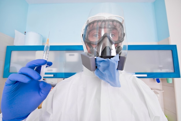Doctor in protective suit uniform and mask holds injection syringe with vaccine.