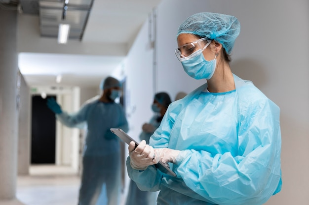 Doctor in protective wear looking at a tablet