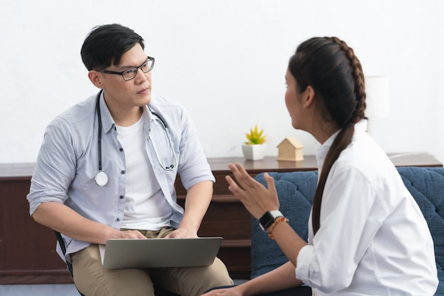 Doctor or psychiatrist talking with asian young woman patient about her illness at healthcare center