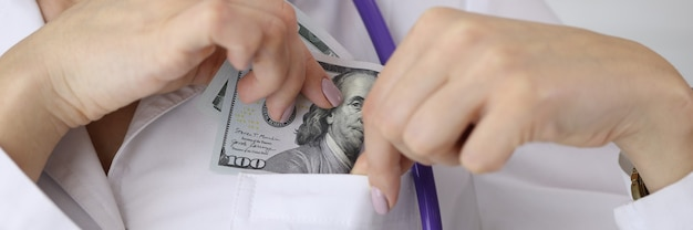 Доктор кладет долларовую купюру в карман униформы в клинике крупным планом
