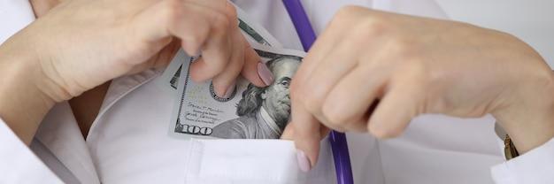 Doctor puting dollar bill in uniform pocket at clinic closeup