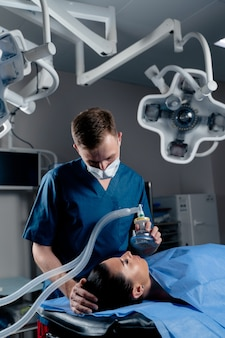 The doctor puts on a mask for artificial ventilation of the lungs in the intensive care unit