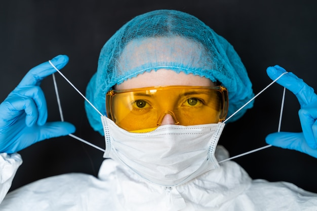 Doctor puts a mask on a black background. pandemic concept of a new coronavirus