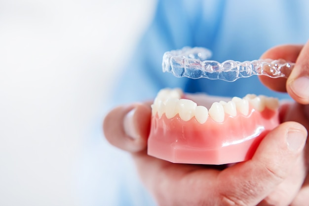 The doctor puts transparent aligners on the teeth of an artificial jaw close up