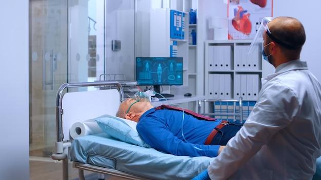 現代の民間クリニックの病院のベッドに横たわっている引退した年配の老人に酸素マスクを置く医者。コロナウイルスcovid-19世界的な健康危機の発生時に呼吸を助ける