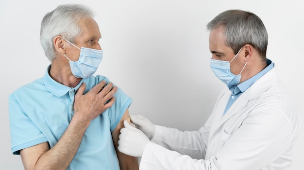 Врач накладывает повязку на пациента мужского пола после введения вакцины
