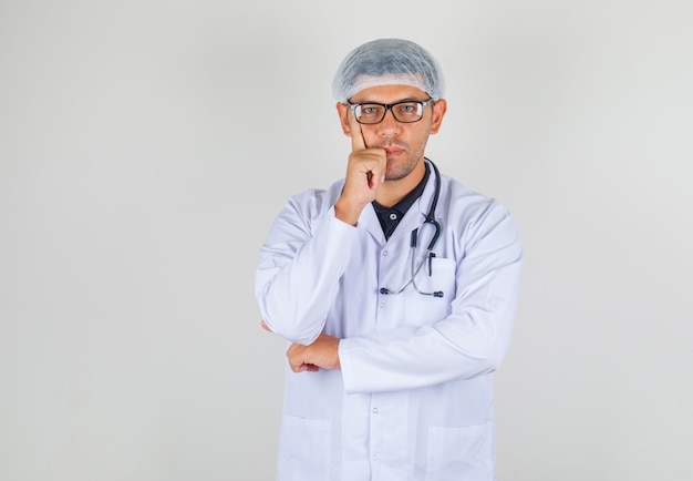 Doctor putting finger to his cheek in white coat and hat and looking positive