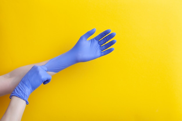 Doctor putting on hand nitrile professional medical purple gloves