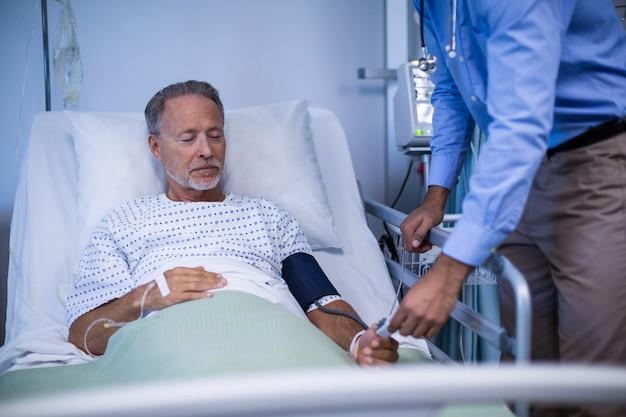 医師が患者の指に心拍数センサーを置く