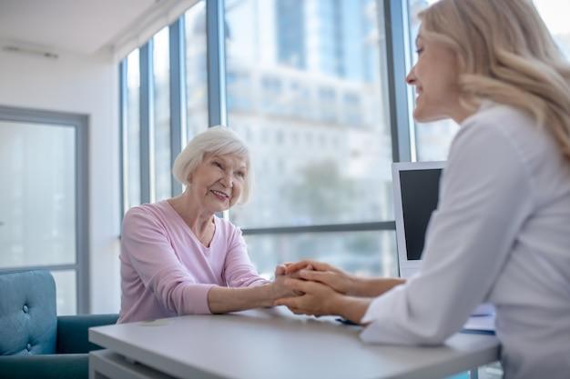 サポートと懸念を示す患者の手に彼女の手を置く医師