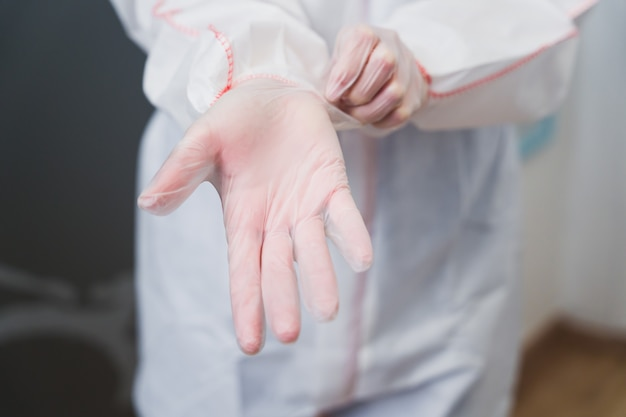 Doctor putting on latex gloves to avoid contagion by the covid 19 virus