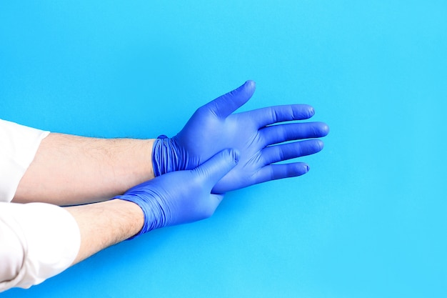 Doctor putting on protective blue gloves.