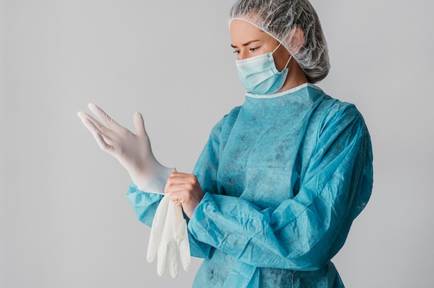 Doctor putting on surgical gloves