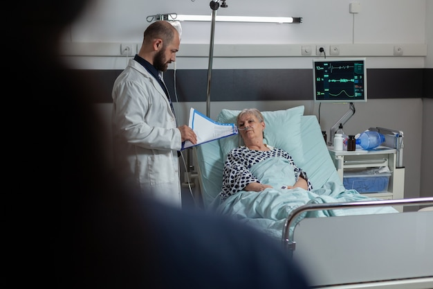 Doctor questioning senior woman laying in hospital bed