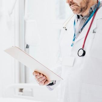 Dottore che legge una cartella clinica di un paziente con coronavirus