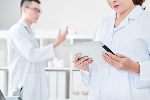 タブレット画面でデータを読む医師