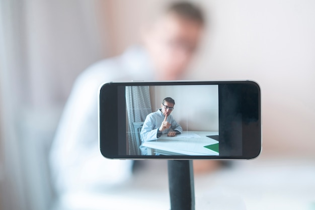ウェブカメラとして電話を使用してオンラインで学生への講義を読んでいる医師