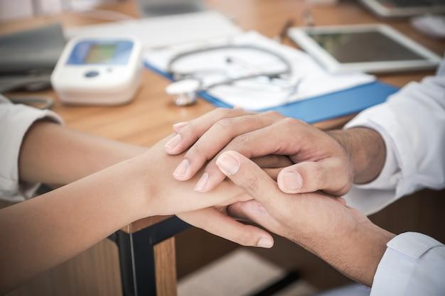 医師は、クリニックの診療所で診察を受けた後、希望のサポートに友好的な励ましと共感を持って若い患者の手を安心させるか、握ります。医療ヘルスケアの概念