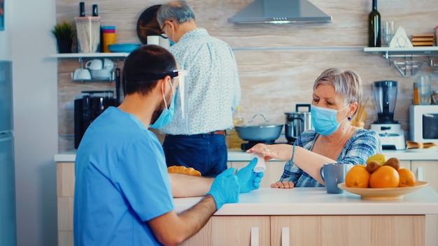医師は、自宅訪問でフェイスマスクとバイザーを着用して、コロナウイルスのパンデミック保持ボトルの間に年配の女性にインフルエンザの錠剤を勧めています。 covid-1を説明する退職した年配のカップルの男性看護師ソーシャルワーカー