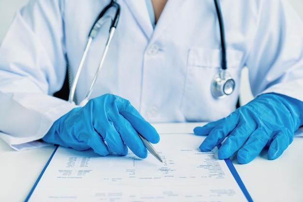 医師が血液検査の検査結果と患者の健康診断の概念の薬の使用法を記録
