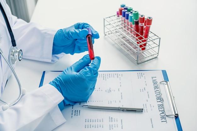 Врач записывает результаты анализов крови и использование лекарств при медицинском осмотре пациента