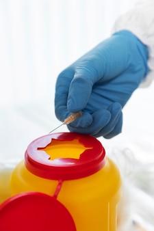 使用済み注射器をリサイクルする医師
