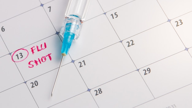 Doctor reminder flu shot in calendar with syringe, medicine and vaccine concept