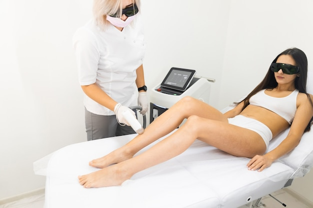 Doctor removes hairs from the skin of the female patients legs