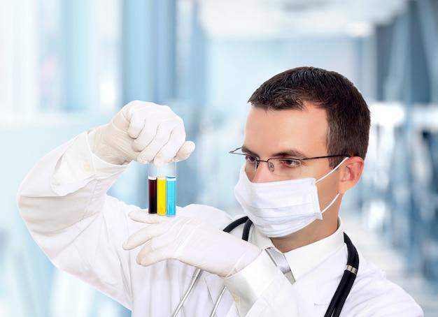 의사는 병원에서 소변으로 의료 테스트 유리를 연구합니다.