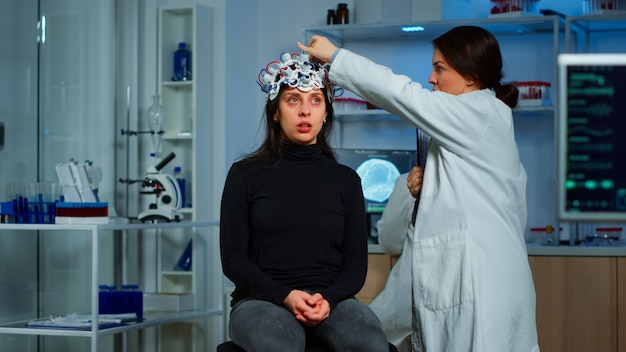 Doctor researcher adjusting eeg headset analyzing patient's evolution after treatment against disease of nervous system. team of scientists working late night in neurological research laboratory