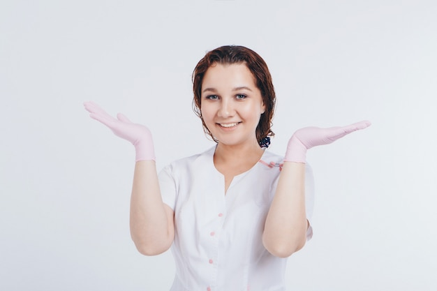 A doctor in rubber gloves holds his palms up. a girl wears a protective gear during an epidemic. ads for antiseptics and medical equipment on a white background. imitation of greeting
