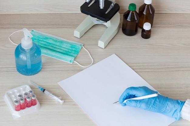 Назначение врача: рука врача в перчатке, ручка в руке, лист бумаги. рядом вакцина, шприц и защитная маска