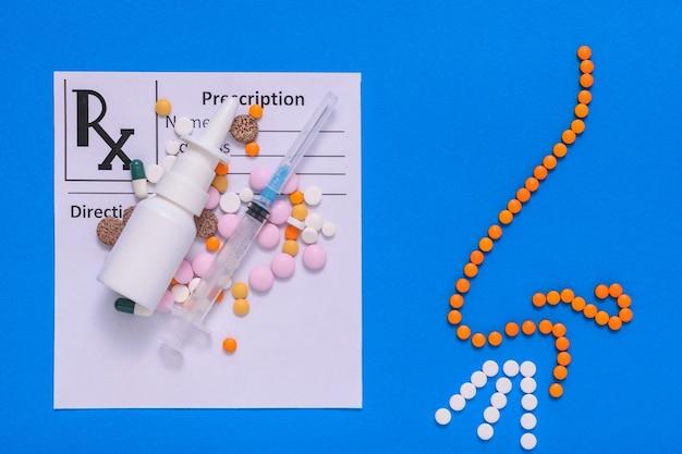 青の背景に薬と錠剤の鼻の図が記載された医師の予約フォーム。鼻やアレルギーの病気の治療の概念。フラットレイ。上部からの眺め。