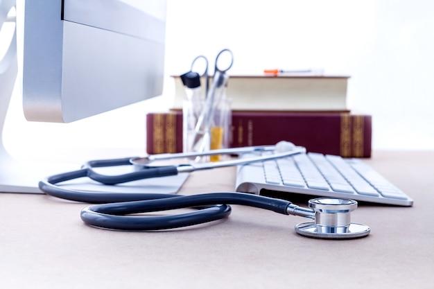 Доктор стол с компьютером и медицинский учебник с малой глубиной резкости.