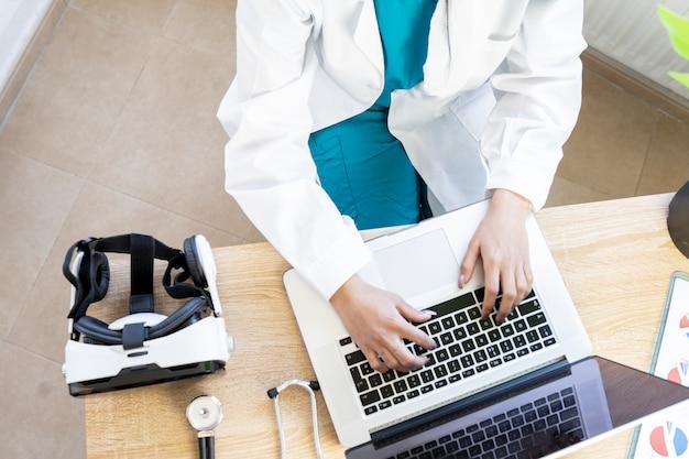 医師が使用しているコンピューターを備えた医師の机