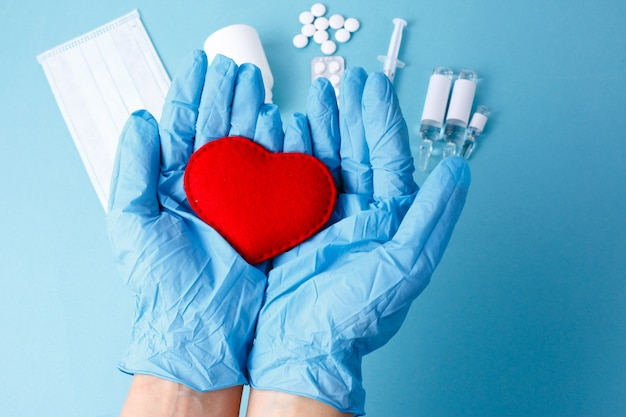 The doctor's gloved hands hold the heart, medications. concept of medicine, treatment of heart diseases