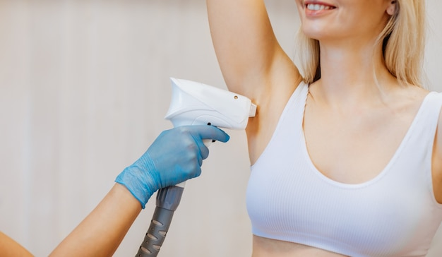Doctor's hand in blue medical glove doing hair removal procedure to the woman's armpit. hair removal concept. copy space.