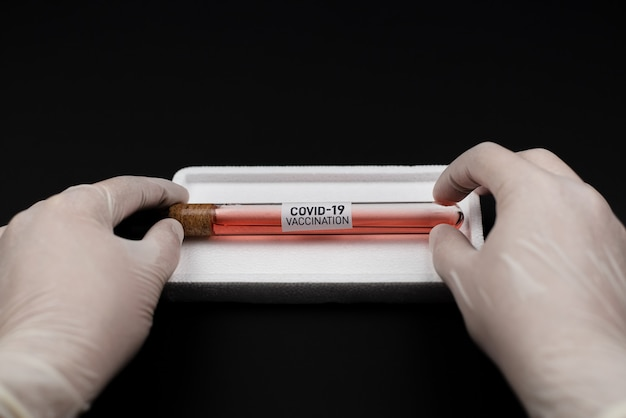 Doctor's hand holding bottle vaccine covid-19 from storage box. medication treatment concept.