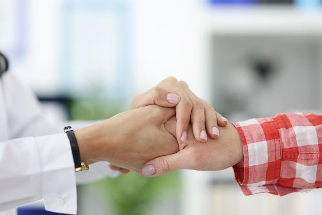 Рука врача держит руку пациента. поддержка врачей во время пандемии