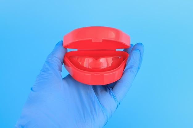 파란색 장갑을 든 의사의 손에 치아 교정을위한 근기능 트레이너가 들어 있습니다.
