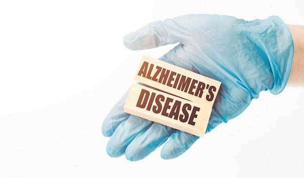 Рука доктора в синей перчатке показывает деревянные кубики со словом болезнь альцгеймера. медицинская концепция.