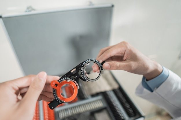 A doctor's hand is holding the experimental lens frame in a room in an eye clinic with the background of the eyeglass frame box