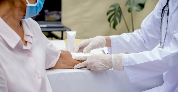 The doctor's hand is making a wound on the arm of an elderly woman who has an accident.