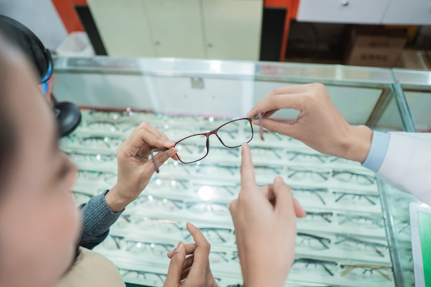 A doctor's hand is showing a recommended pair of glasses to a female patient who has undergone an examination at an eye clinic