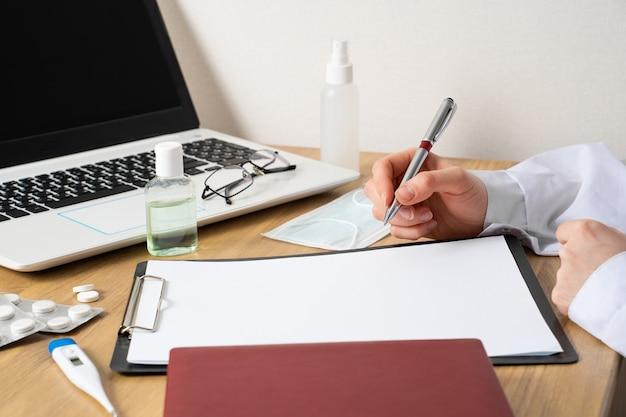 펜으로 의사의 손은 종이 홀더, 의료용 마스크, 항균 젤, 알약 및 컴퓨터의 종이에 무언가를 쓸 것입니다.